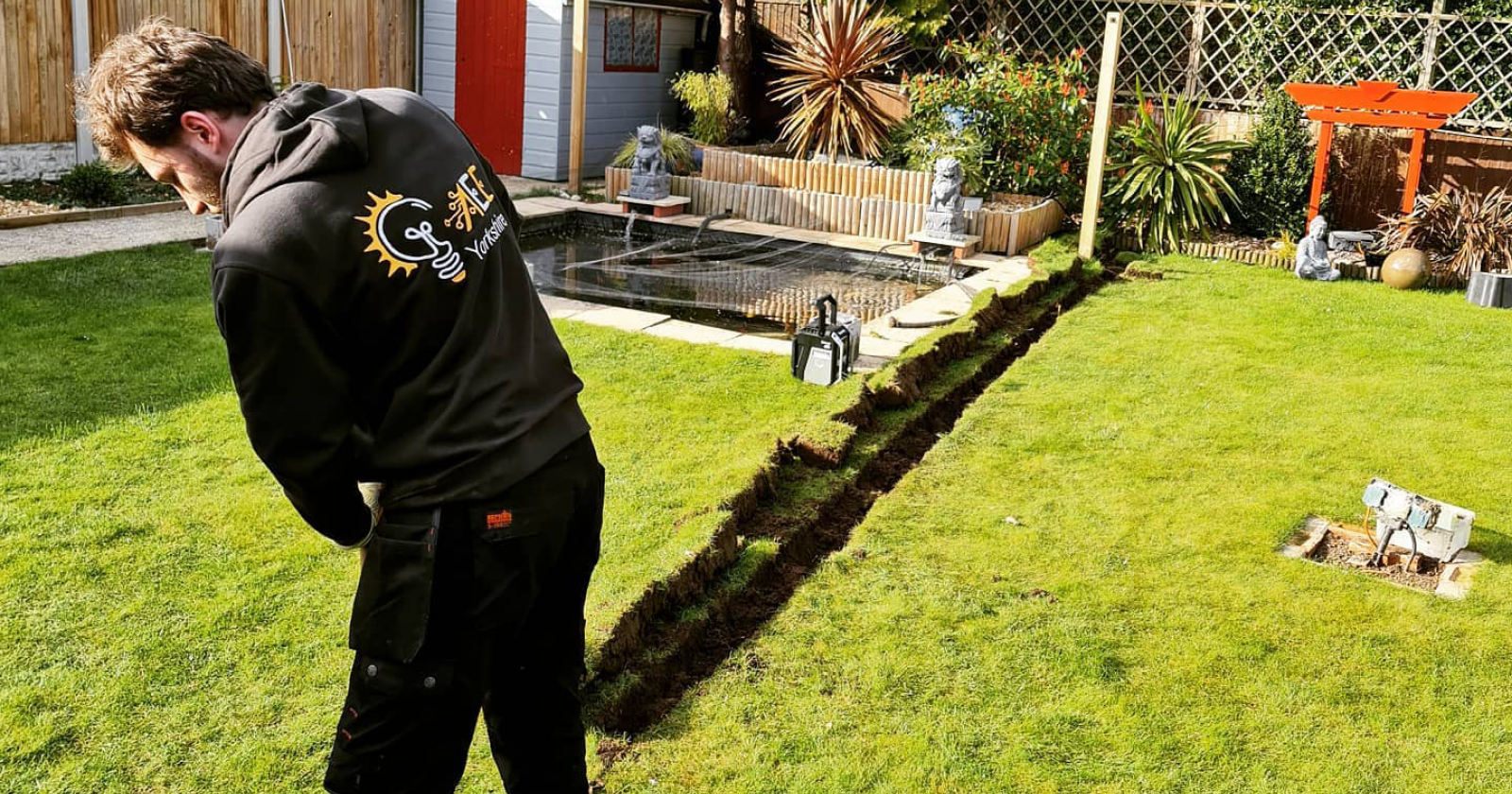 electrician from aee yorkshire digging a trench in the backyard