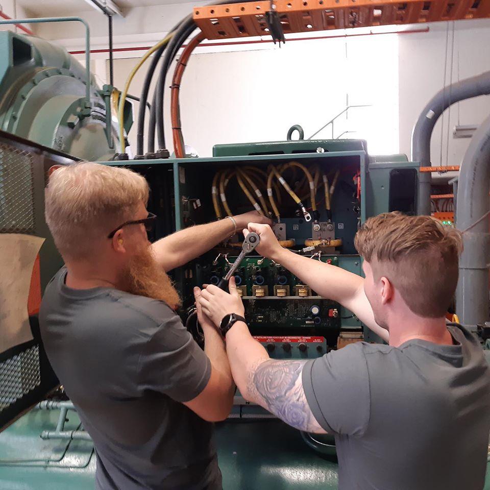 Two men tightening a bolt on a chiller installation