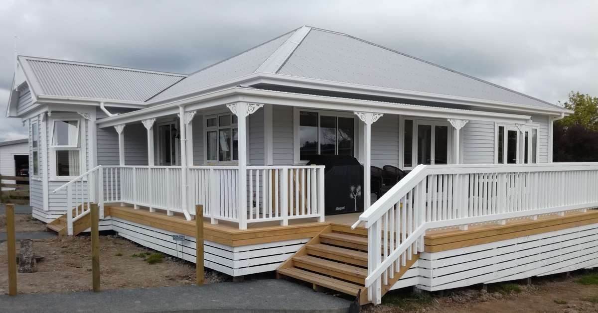 Apex Construction home renovation of a wrap around deck on a beautiful light grey villa