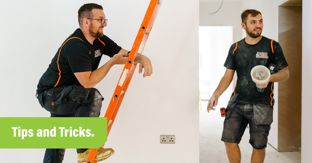Electrician leaning on ladder looking at app on phone