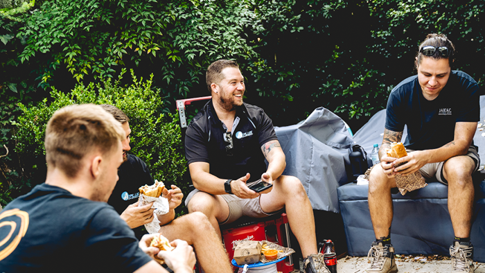 Blog-How To Be a Good Landscaper-group of people sitting around having lunch and smiling
