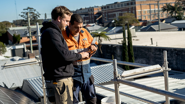 two men on construction roof looking at phone