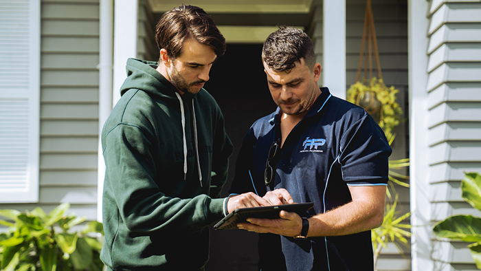plumber and customer standing outside house looking at tablet together
