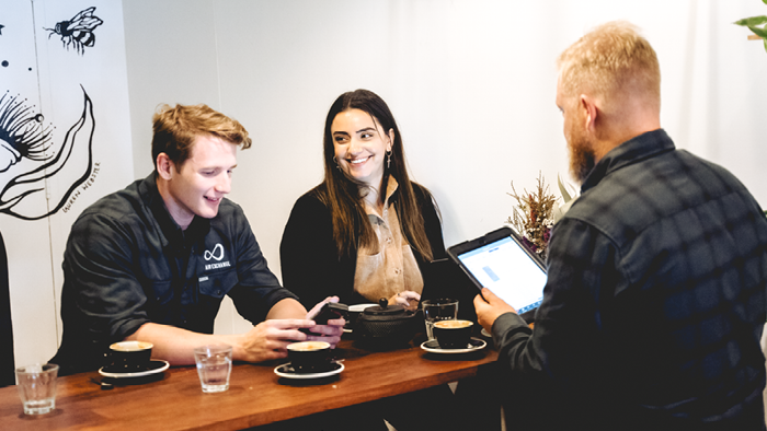 three people sitting in a cafe smiling and looking at devices