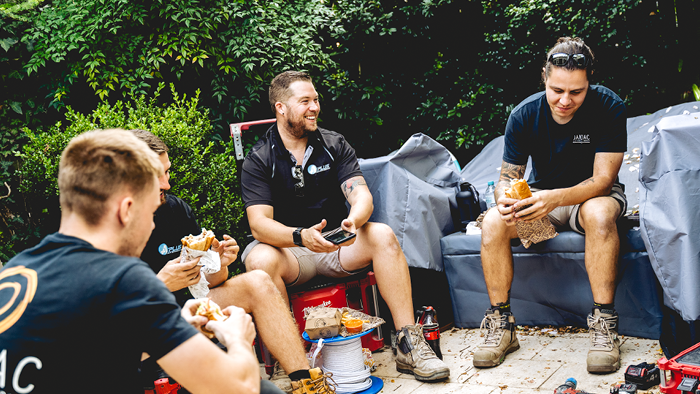 group of tradies sitting together outside having lunch