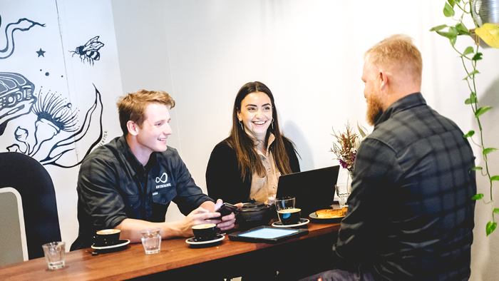 three people sitting at cafe and smiling