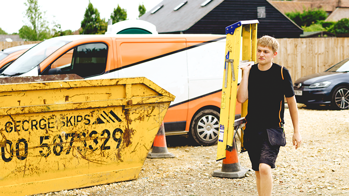 young man carrying step ladder on shoulders walking past a large skip bin
