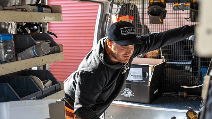 man looking inside work van filled with tools
