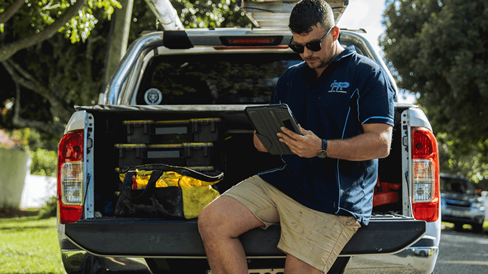 man sitting on tray of ute working on device