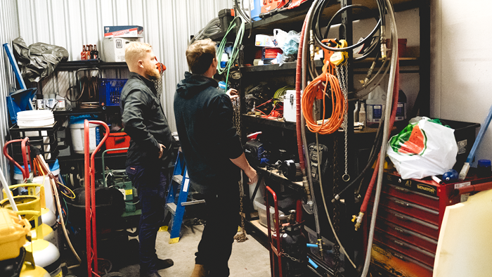 two men in tool shed looking at tools on shelves