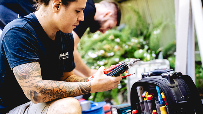 man looking at phone in hand while holding other tools