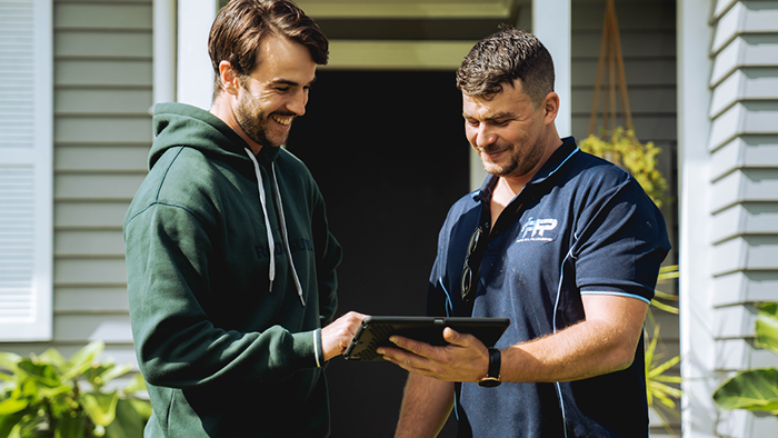 business owner looking at device with customer and smiling