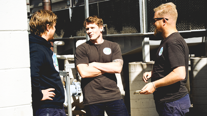 three men standing outside surrounded by metal building structure having a conversation