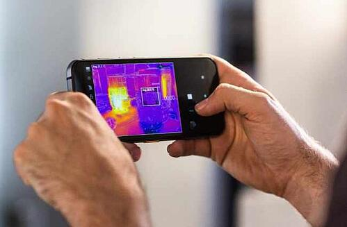 Holding a CAT phone in landscape orientation and using the thermal view feature