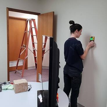 An electrician using a stud finder on a wall before hanging a television
