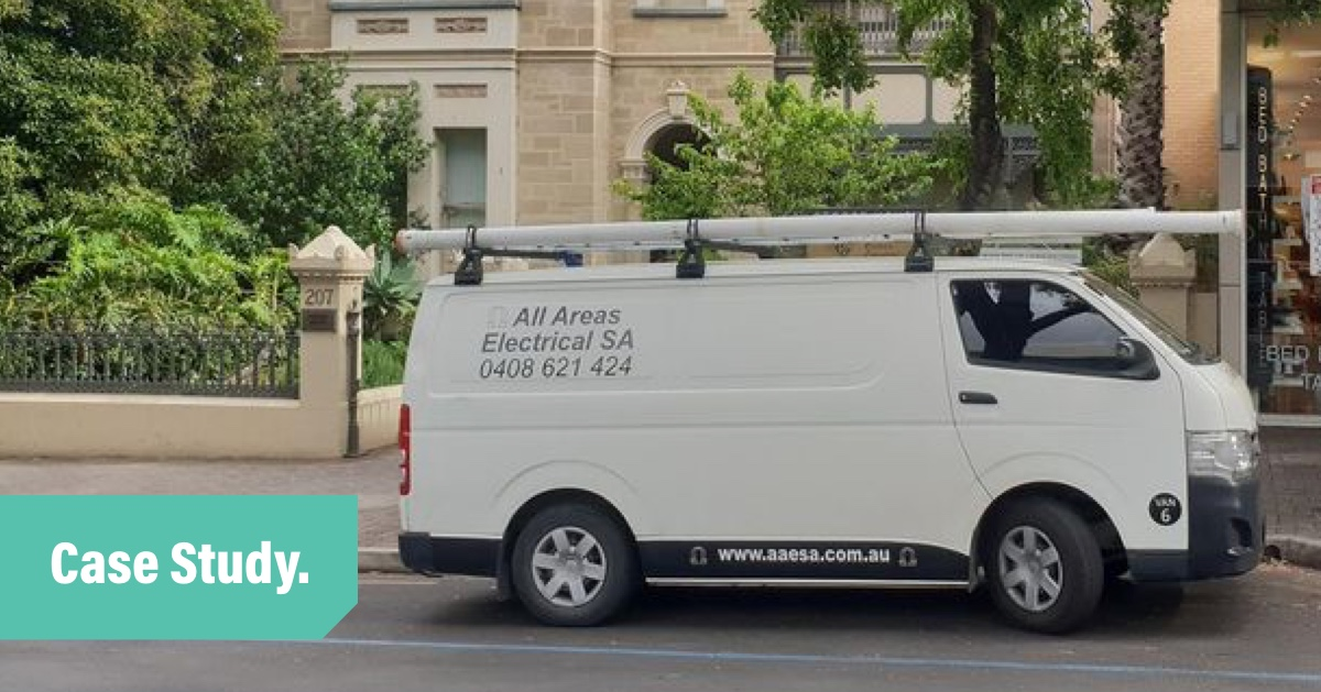 A photo of the all areas electrical white work van parked in front of a heritage brick building