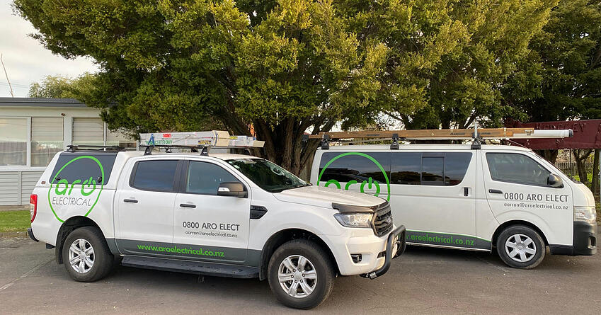 The Aro Electrical fleet, a white ute and a white van, parked together in front of a school building