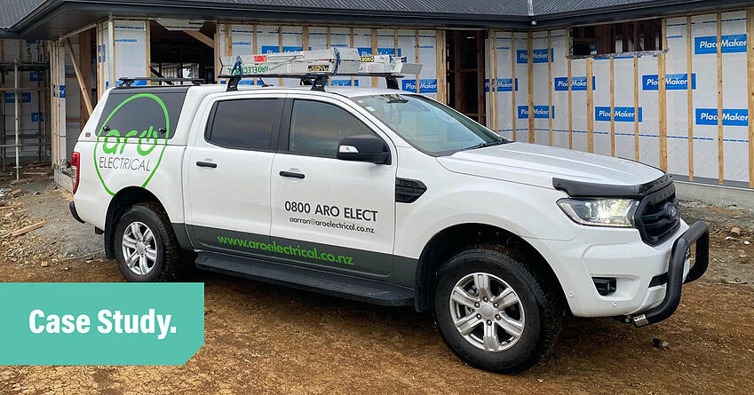 Aro Electrical's white ute parked on the dirt on a building site in front of a partly constructed house. Image overlayed with the words Case Study.