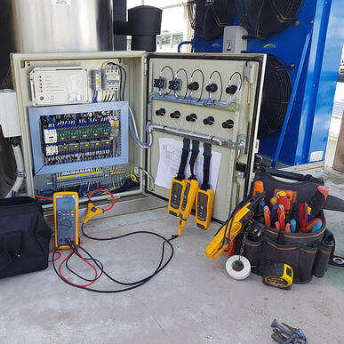 A photo of the inside of an electrical cabinet hooked up to testing equipment. Next to it sits a very full tool bag.