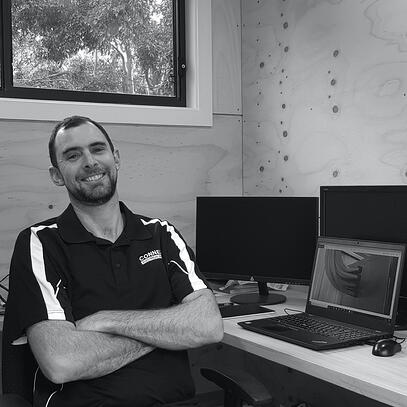 A black and white photo of electrician, Kiah, smiling with arms crossed and sitting in his office in front of a laptop.