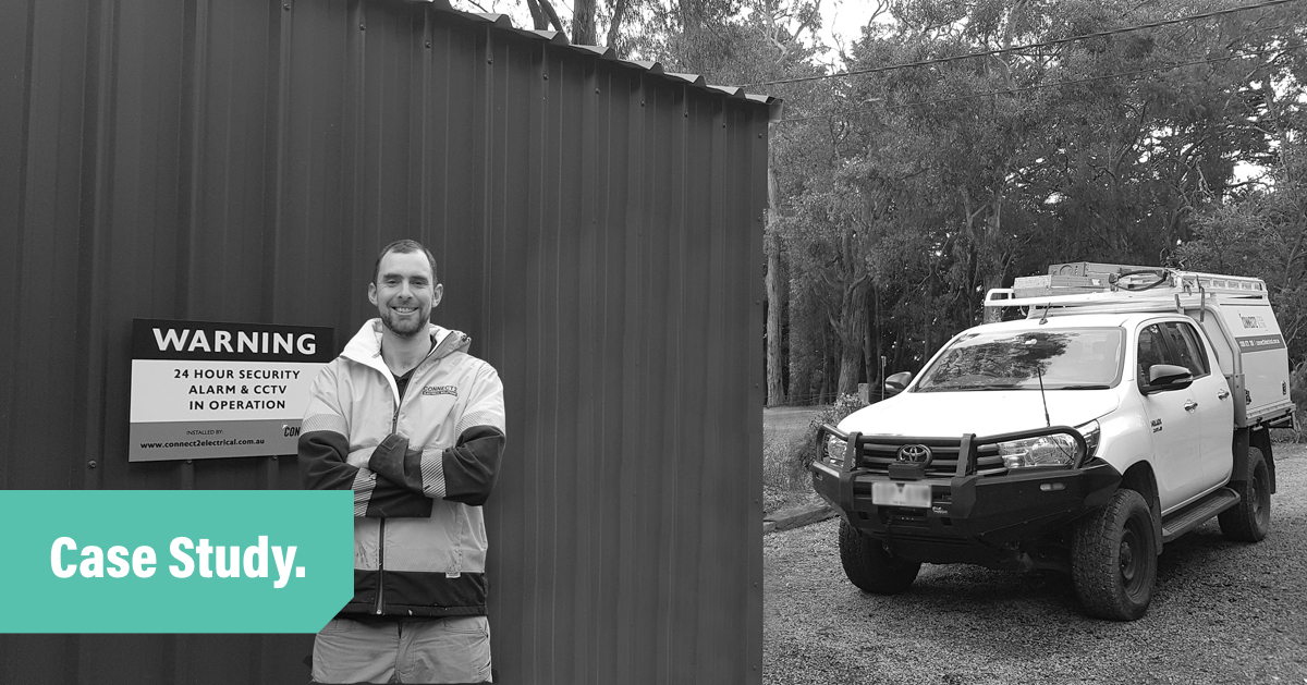 A black and white photo of electrician and tradify customer Kiah smiling and standing with arms crossed in front of a dark coloured shed