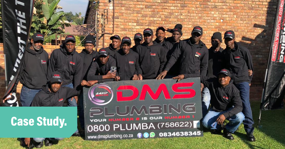 DMS Plumbing Team holding sign