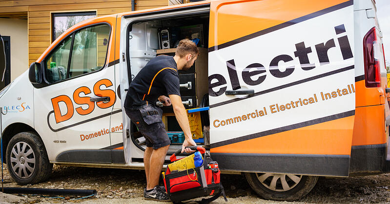 A photo of an electrician loading tools into a van