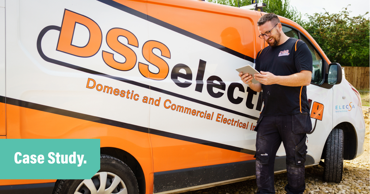 A photo of Dan standing in front of his orange van, smiling and looking at an ipad