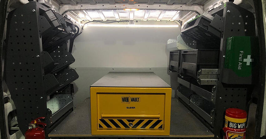 A photo showing the inside of the electrician's van lined with shelves, a yellow metal van vault, and a dark green first aid kit