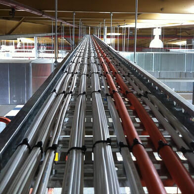 A photo of electrical cables running along an commercial building ceiling
