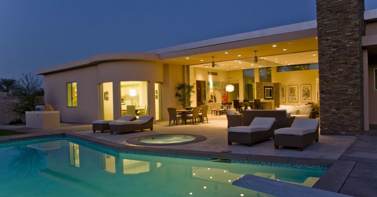 A flash, single level house lit up at night with great lighting by the Tweed team. The lights reflect into a swimming pool.