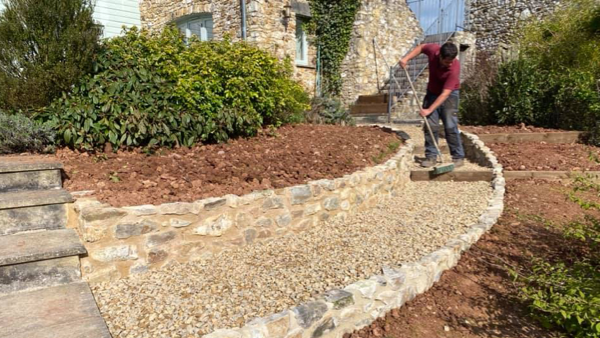 CaseStudy_jake_smith_construction_worker sweeping steps on rock path in a garden