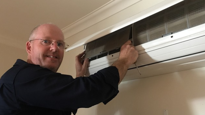 greg begelhole looking at camera while standing in-front of a wall mounted heat pump