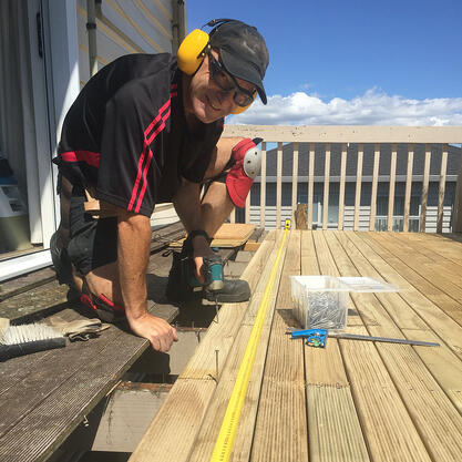 A photo of Andy smiling while building a new deck