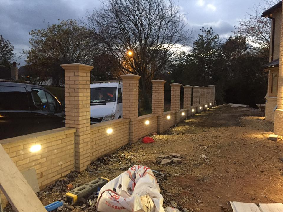 Photo of a complete outdoor light installation by JJ Electrical. Lights have been installed into a new brick fence.