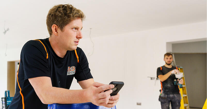 An electrician uses his phone to do admin on the go