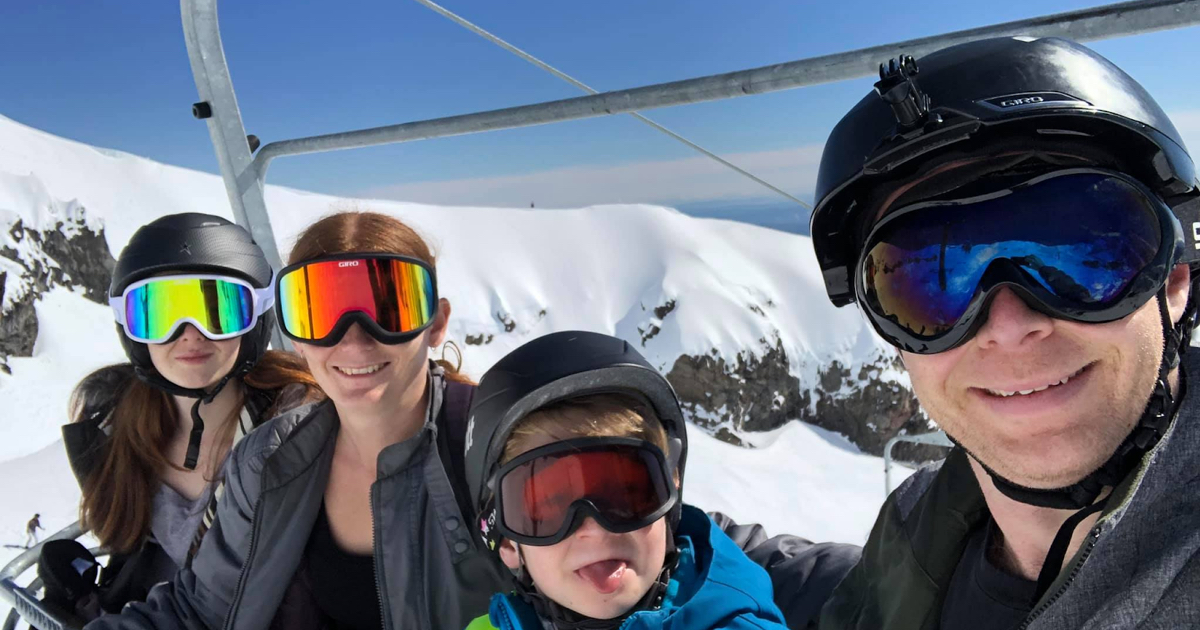 Karl with his wife, daughter and son, sitting on a ski lift travelling up a snowy mountain.