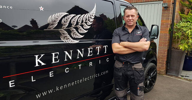 An electrician standing in front of his black with a sign for Kennett Electrics and a silver fern emblem