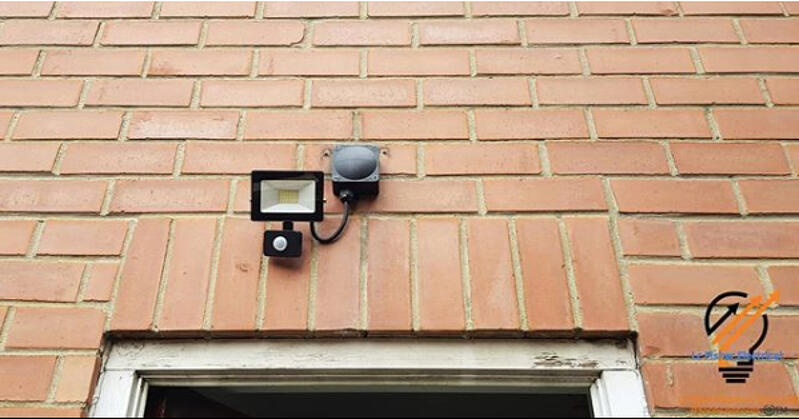 Close up photo of an outdoor sensor light on the exterior of a brown brick building