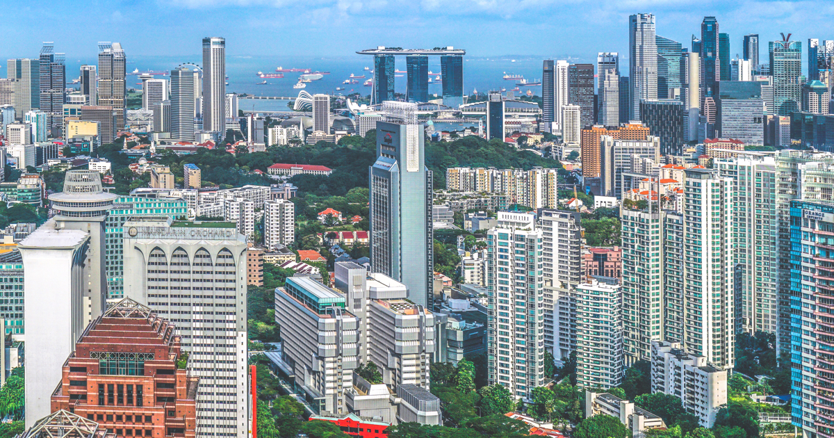 Photo of Singapore with lots of highrise buildings and the sea in the distance
