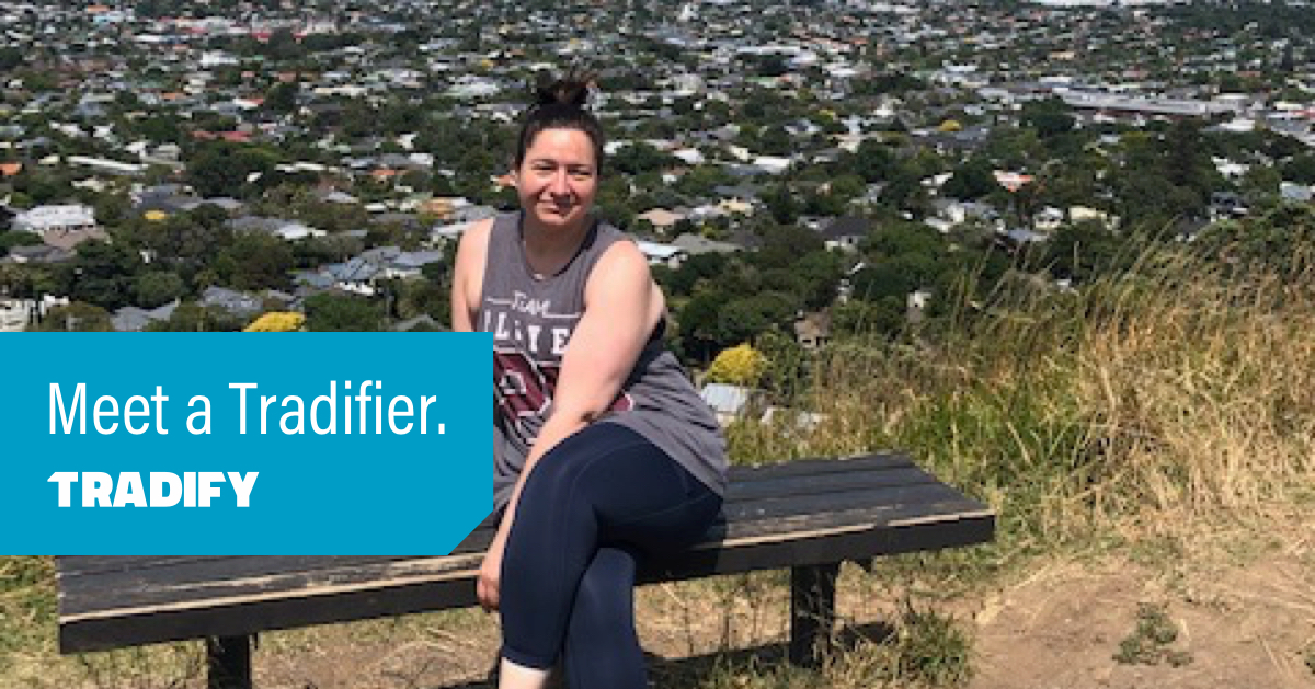Christine sits on a bench on the top of one of Auckland's mountains