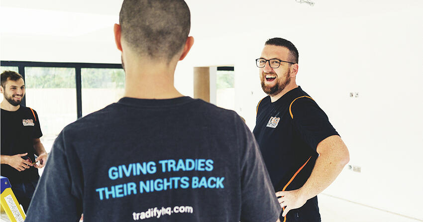 """Three guys having a laugh at a job site. One wears a Tradify T-Shirt that reads """"giving tradies their nights back""""."""