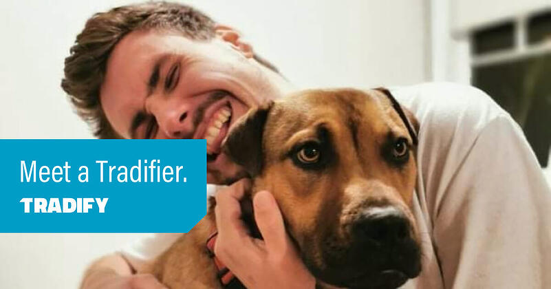Meet a Tradifier heading with a photo of Tom hugging a dog. The dog is not amused.