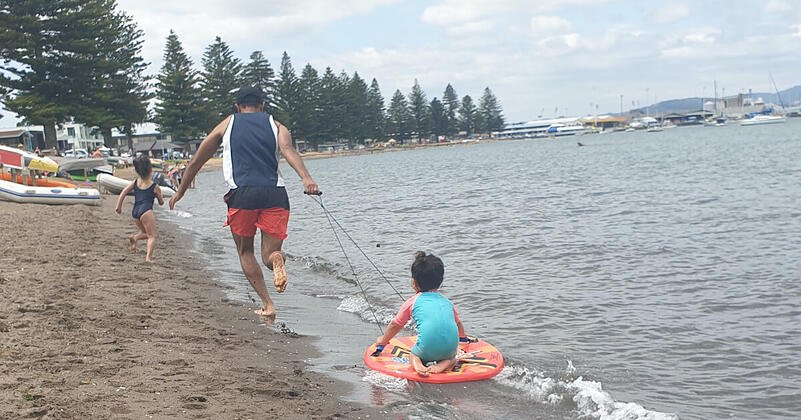 Victor chases one daughter along the beach shoreline while pulling the other who is sitting on a boogie board.