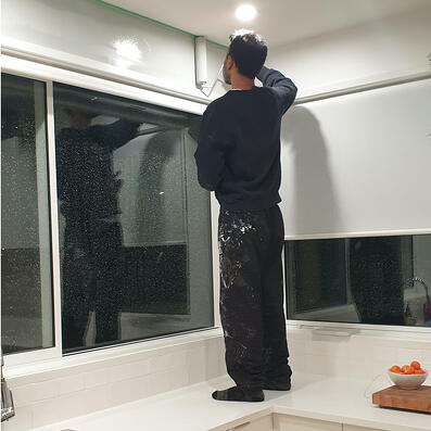 Victor stands on his kitchen bench while careful painting the top of the wall with a roller