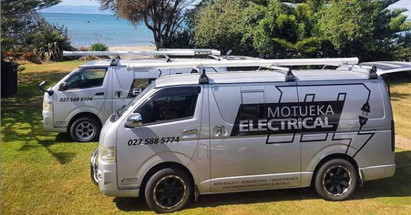 Two silver Motueka Electrical vans parked up on the grass next to a sandy beach