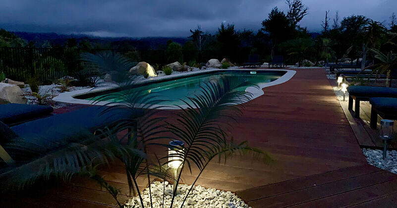 A beautiful new inground pool surrounded by decking and great lighting, lit up at night