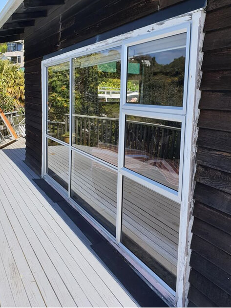 New white aluminium windows on a black weatherboard house