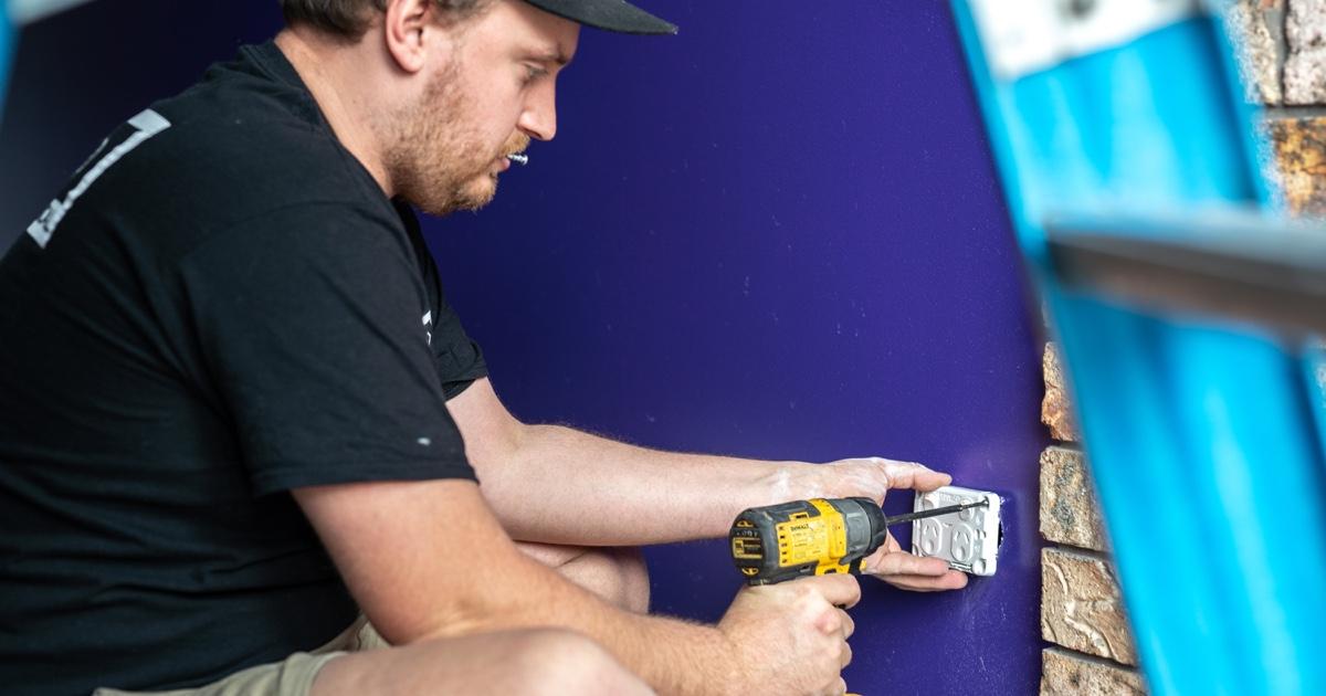 electrician installing a power socket with a DeWalt drill