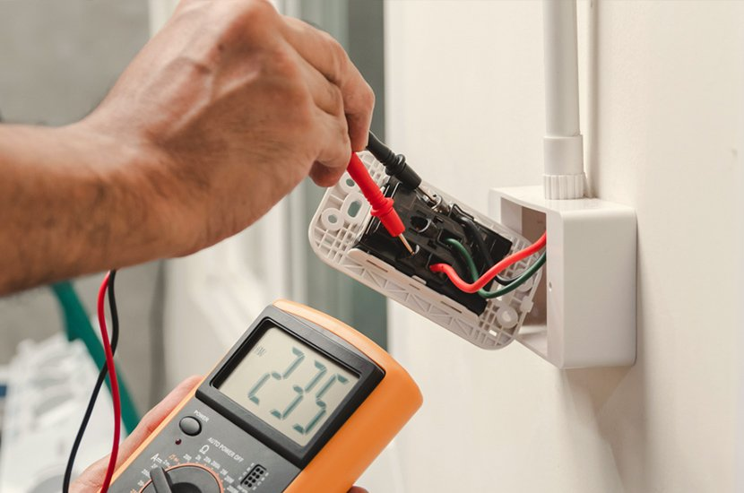 A photo of Freedom Electrical testing a power outlet. The meter reads 235.
